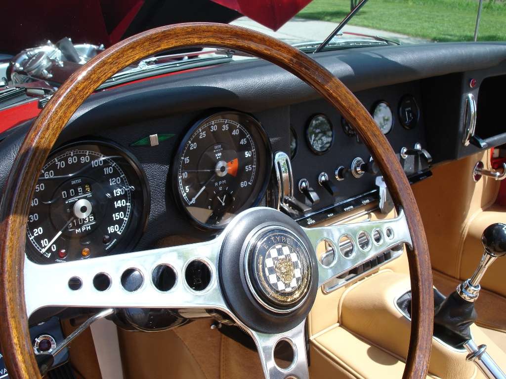 Up close shot of the steering wheel of a 1967 Jaguar XKE red convertible