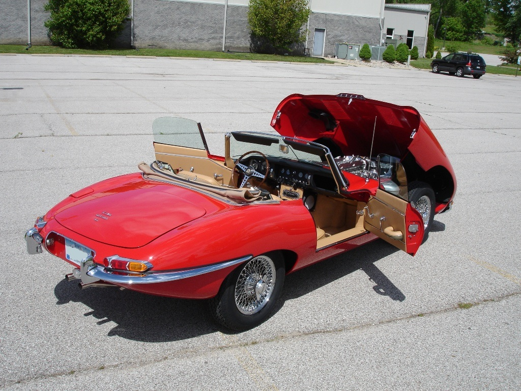 Back view of a 1967 Jaguar XKE red convertible with the hood open and doors open